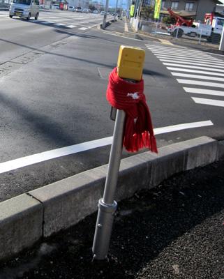 赤い毛糸のマフラーをまとった歩行者用押しボタン