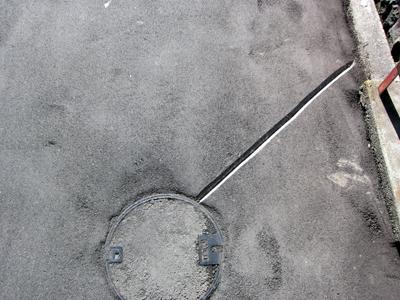 マンホールからアスファルトをまっすぐに伸びる線