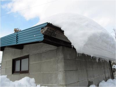 屋根からずり落ちそうでずり落ちないで垂れ下がる大雪の名残